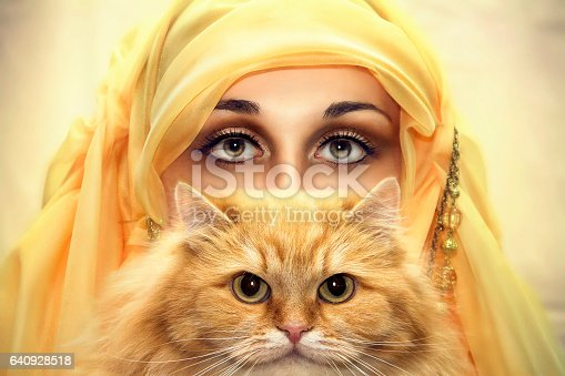 Oriental girl in a burqa with a red cat