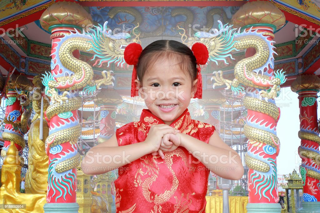 2333943a89396 Asian girl in Cheongsam respecting on traditional Chinese new year festival  on Chinese background. - Stock image .