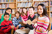 istock Asian girl in school library smiling by reading group 183364525