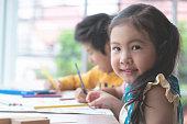 Asian girl is drawing in kindergarten art classroom