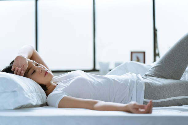 asian girl is headache in bed. - metabolic syndrome stock photos and pictures