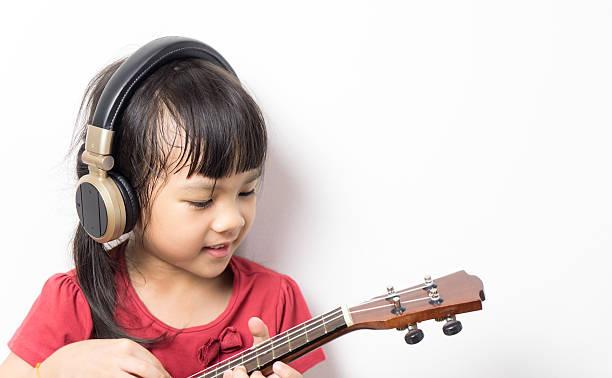 asian girl is playing guitar headphone on white background. - ukulele songs stock-fotos und bilder