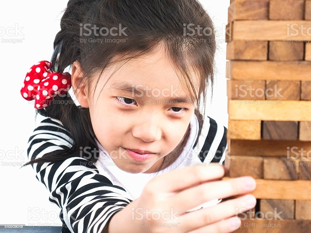 Asian girl is playing wood blocks tower game stock photo