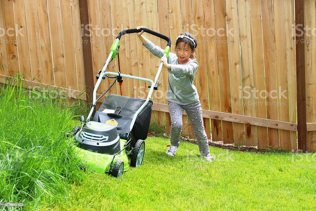 Asian Girl is pushing electric lawn mower stock photo