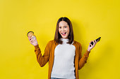 istock Asian girl is surprised she is excited. In mobile phone with coffee yellow background, studio 1030391210