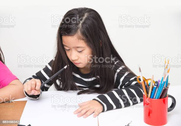 Asian girl kid concentrates on drawing cartoons by pencil in art picture id683466342?b=1&k=6&m=683466342&s=612x612&h=p j3axwebsgndfuxiclntv9mtovipgzgojpemerflsq=