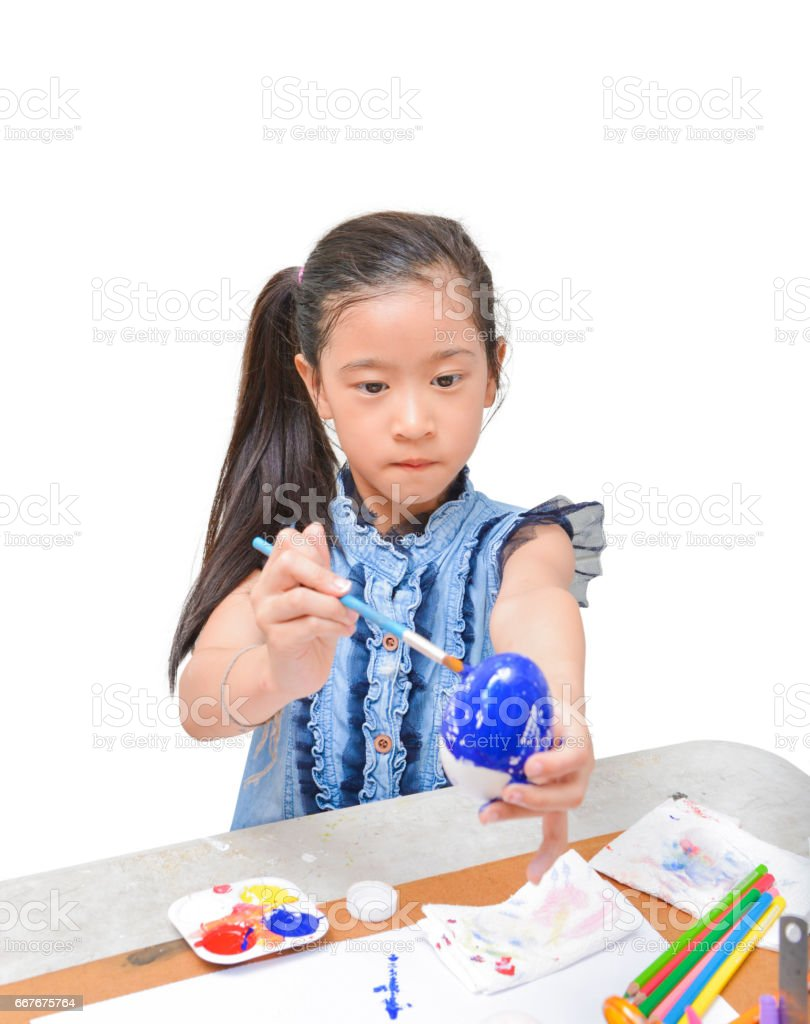 Asian girl kid concentrates on painting easter egg with brush in blue color isolated on white background stock photo