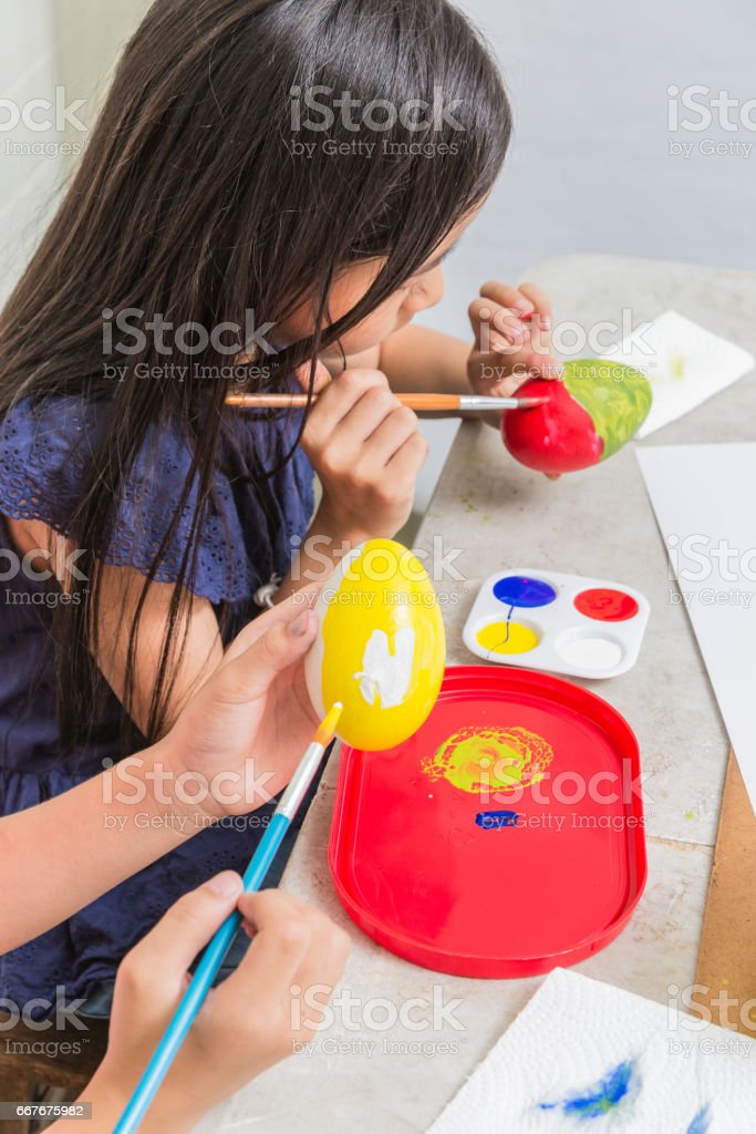 Asian girl kid painting easter egg by brushes stock photo