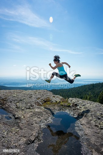903015102 istock photo Asian Girl Leaping and Jumping over Puddle on Mountain Top 486401624