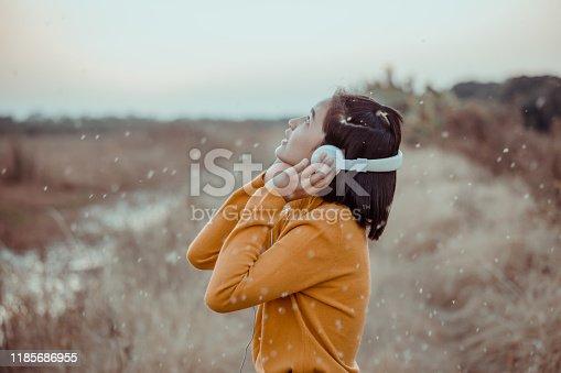 Asian girl listening music with headphones