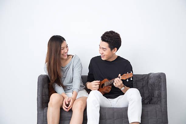 asian girl listening to asian boy play ukulele - ukulele songs stock-fotos und bilder