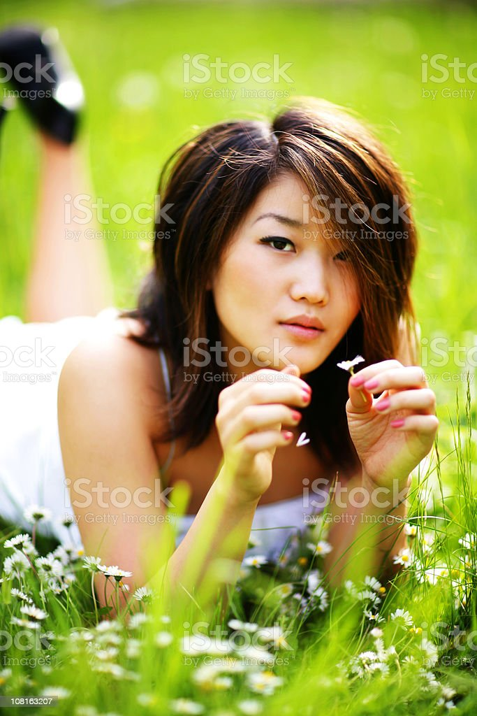 Asian Girl Lying on Stomach Picking Apart Flower royalty-free stock photo