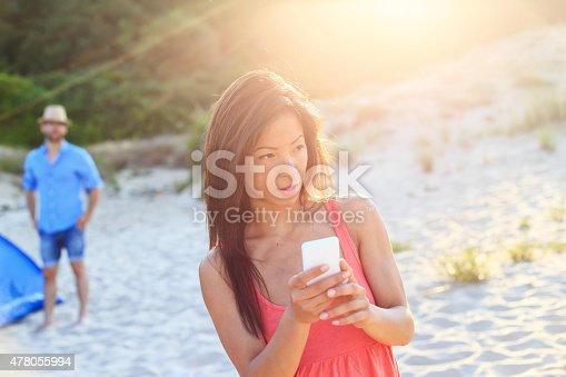 Woman on the beach texting a smart phone
