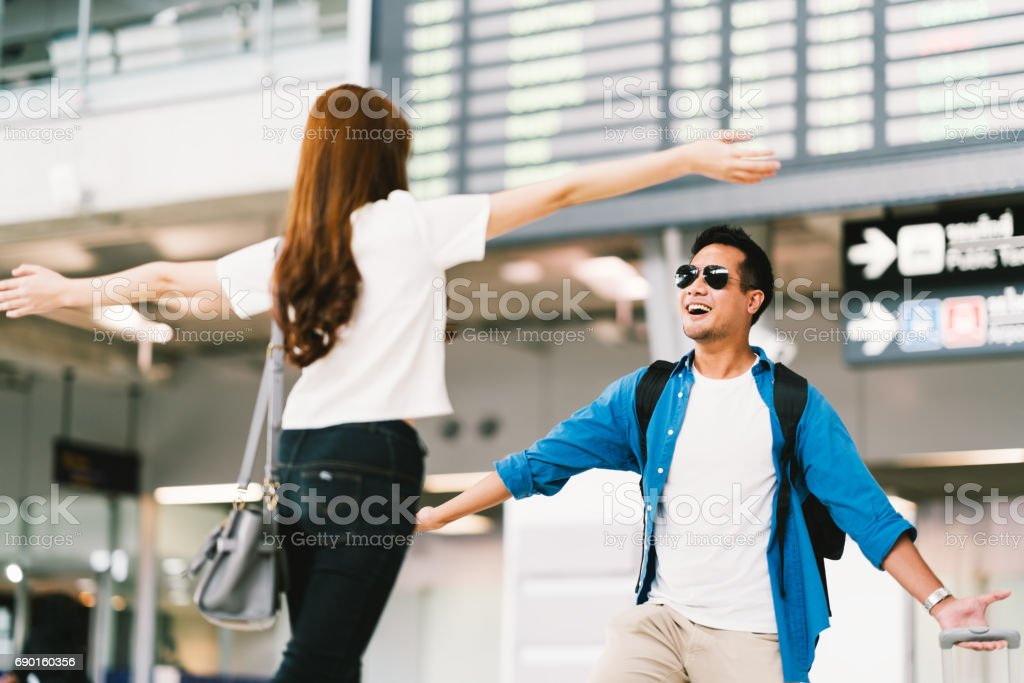 Asian girl picking up her boyfriend at airport's arrival gate, welcomes back home from studying or working abroad. Young couple love and hug, honeymoon, or traveling concept stock photo