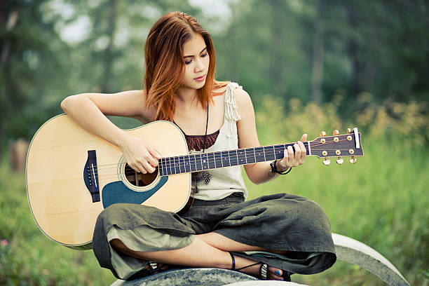 royalty free hippie girls with guitar in a forest pictures images