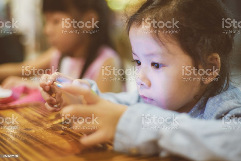 Asian girl playing or use smartphone , child addicted phone. Selected focusing . stock photo