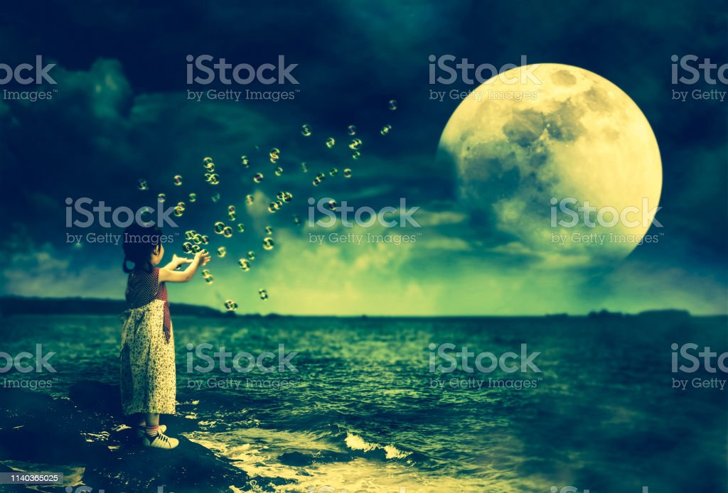 Asian girl playing with soap bubbles. Super moon behind partial cloud on sky. stock photo