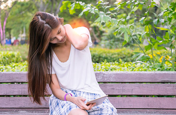 Chica asiática lectura de comprimido con hombro y dolor de cuello - foto de stock