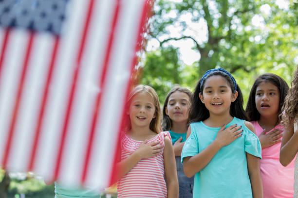 asiatin rezitiert versprechen der treue, amerikanische flagge mit freunden - eid stock-fotos und bilder