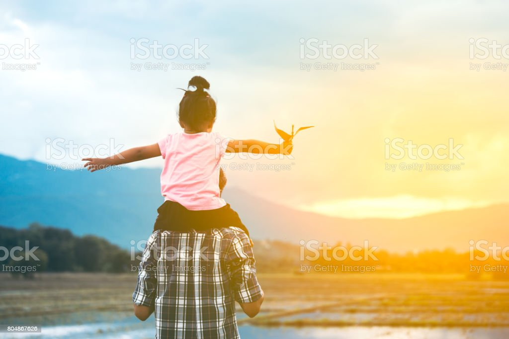 asian girl riding on father's shoulder and playing with toy paper airplane stock photo