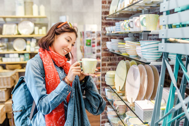 asian girl shopping for kitchenware in retail store - household equipment stock pictures, royalty-free photos & images