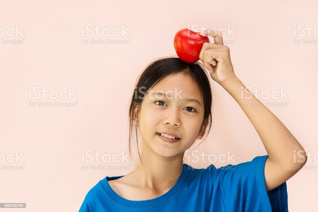 Asian girl showing heart ball plastic at home. stock photo