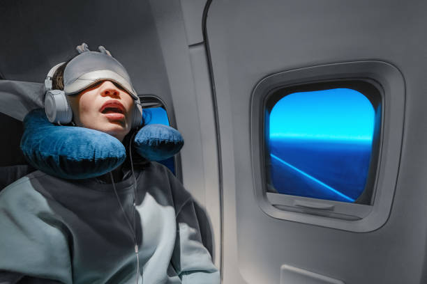 Asian girl sleeping in her seat on the plane near the window in a mask and with a pillow to sleep. The concept of travel with comfort and jetlag Asian girl sleeping in her seat on the plane near the window in a mask and with a pillow to sleep. The concept of travel with comfort and jetlag jet lag stock pictures, royalty-free photos & images