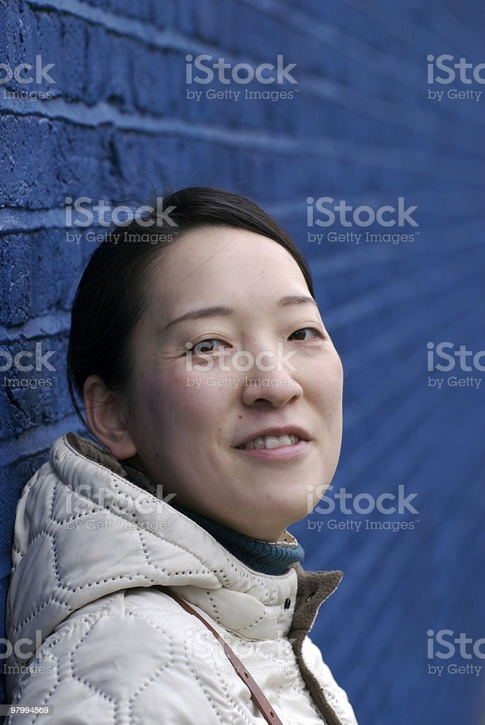 Asian girl standing against blue wall, copy space royalty-free stock photo