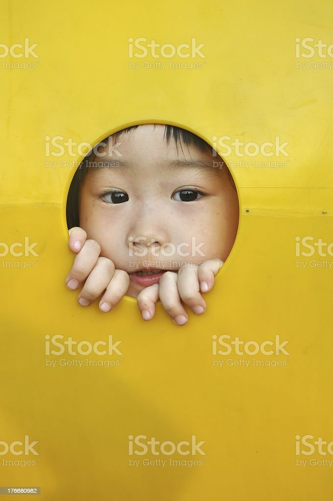 asian girl sticks face through a hole in playground royalty-free stock photo