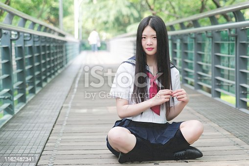 Asian girl student in school uniform Japanese style, sit on a wooden bridge in sun shine, looking and smiling at camera with hands on her black long hair.