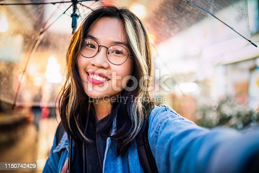 Asian girl taking a selfie in rain.