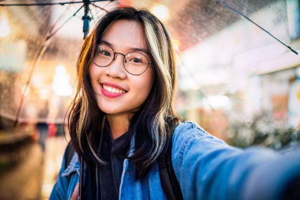 aziatisch meisje met een selfie in de regen - selfie girl stockfoto's en -beelden