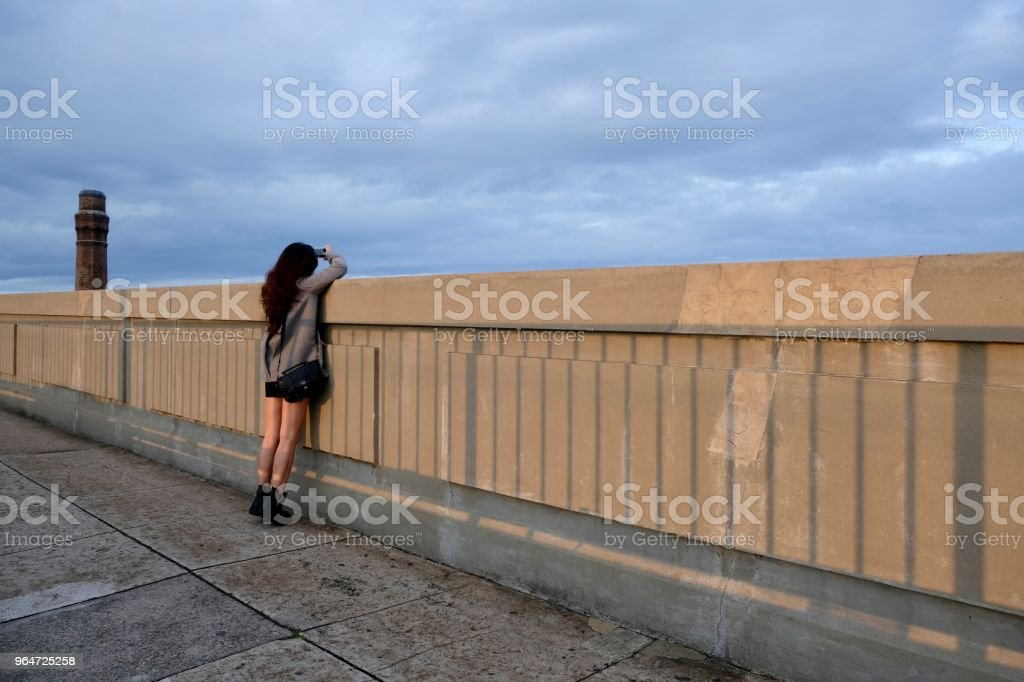 Asian girl taking photo on bridge against sky. royalty-free stock photo