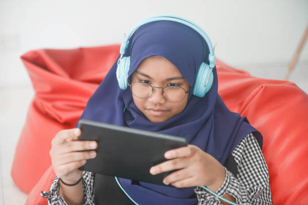 Asian girl using digital tablet at home stock photo