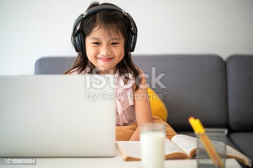 Asian girl using laptop for online study during homeschooling at home during Coronavirus or Covid-19 virus outbreak situation