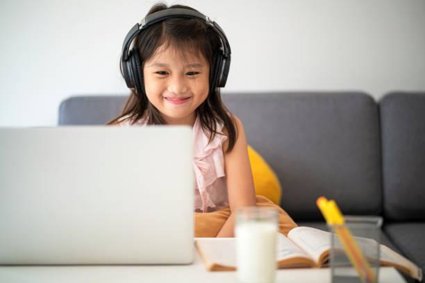 asiatische mädchen mit laptop für online-studie während homeschooling zu hause - homeschooling stock-fotos und bilder