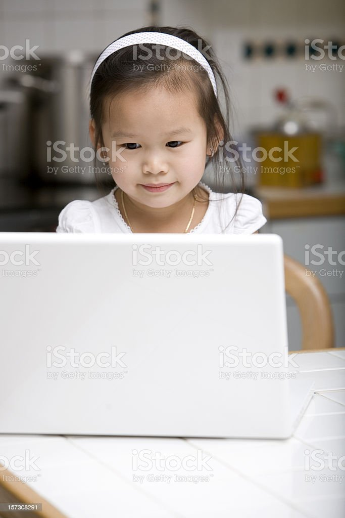 Asian Girl Using Laptop in Home Kitchen, Close Up, Copyspace royalty-free stock photo