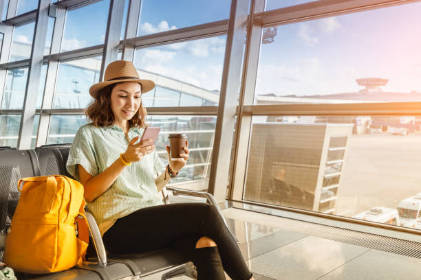 Asian girl waiting for departure at the airport on your vacation. Uses a smartphone and drinks coffee stock photo