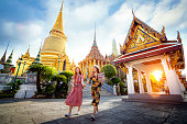 Asian girl walk in Wat phra kaew and grand palace travel in Bangkok city, Thailand