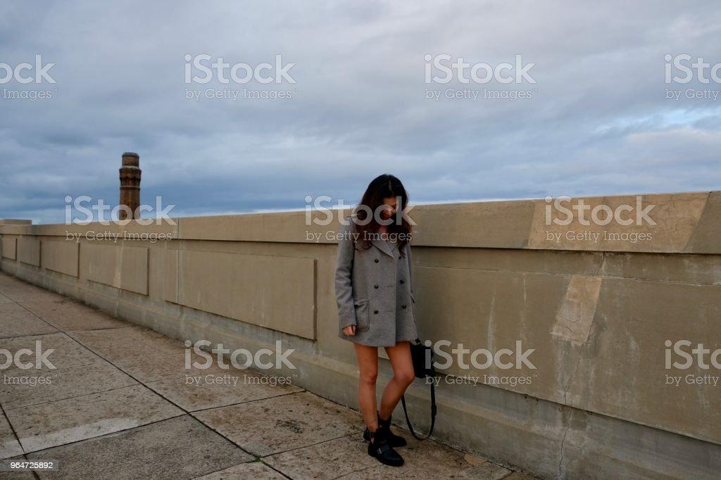 Asian girl walking across bridge against sky. royalty-free stock photo