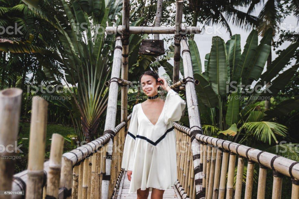 Asyalı kız asma bambu köprü Ubud Bali yürürken. Canggu lüks villada yeşil tropikal Bahçe çevresinde. royalty-free stock photo