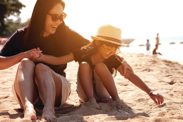 Asian girl wearing a hat and sunglasses and his mother sitting on the sand at the beach stock photo