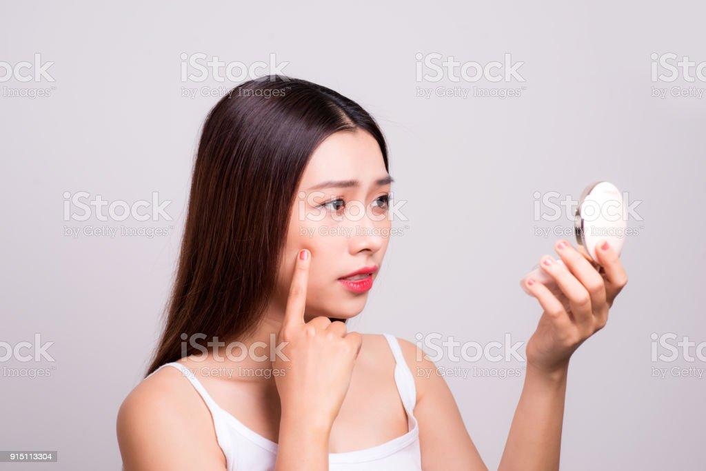 Asian girl who checks her skin, skin care, acne treatment. stock photo