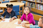 istock Asian girl with classmates in elementary school, writing 1194315102