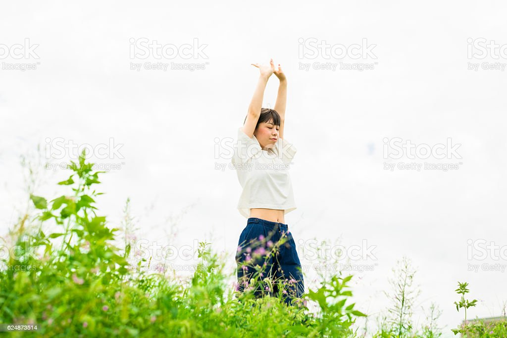 Oriental girl with free atmosphere in the green field ストックフォト
