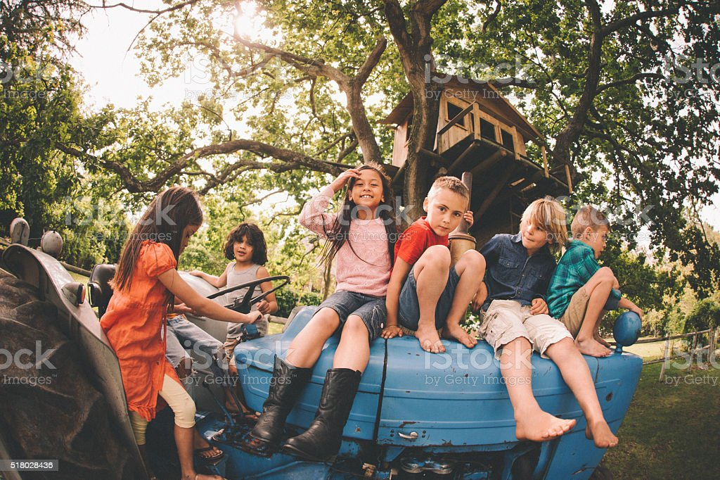 Asian girl with friends playing on an old tractor stock photo
