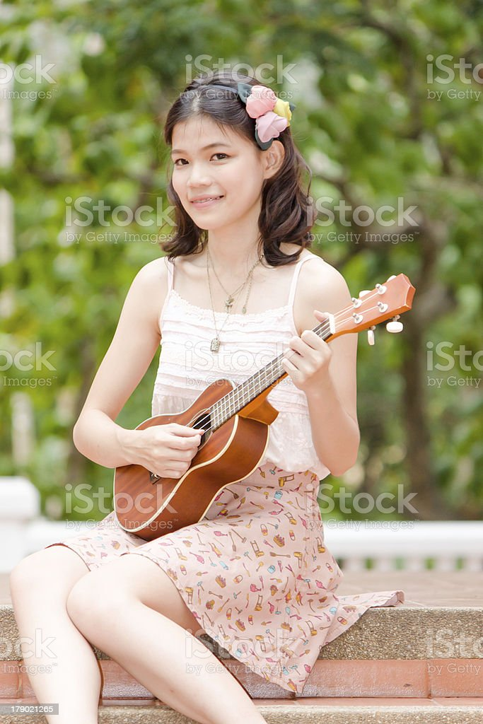 Asian girl with ukulele guitar outdoor stock photo