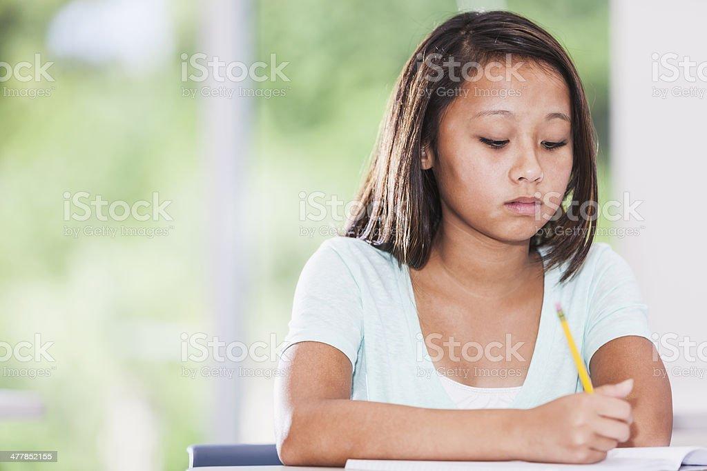 Asian girl writing in class royalty-free stock photo
