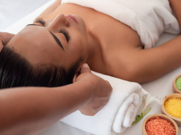 Asian girls are a relaxing ear massage in the Spa Salon. Thai massage for health stock photo