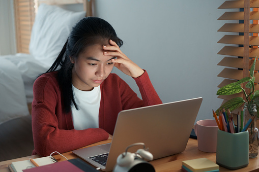 Asian girls are sitting stressed studying online with a tutor on a laptop while sitting in the bedroom at home night. Concept online learning at home